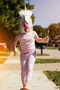 Girl skipping while wearing unicorn mask