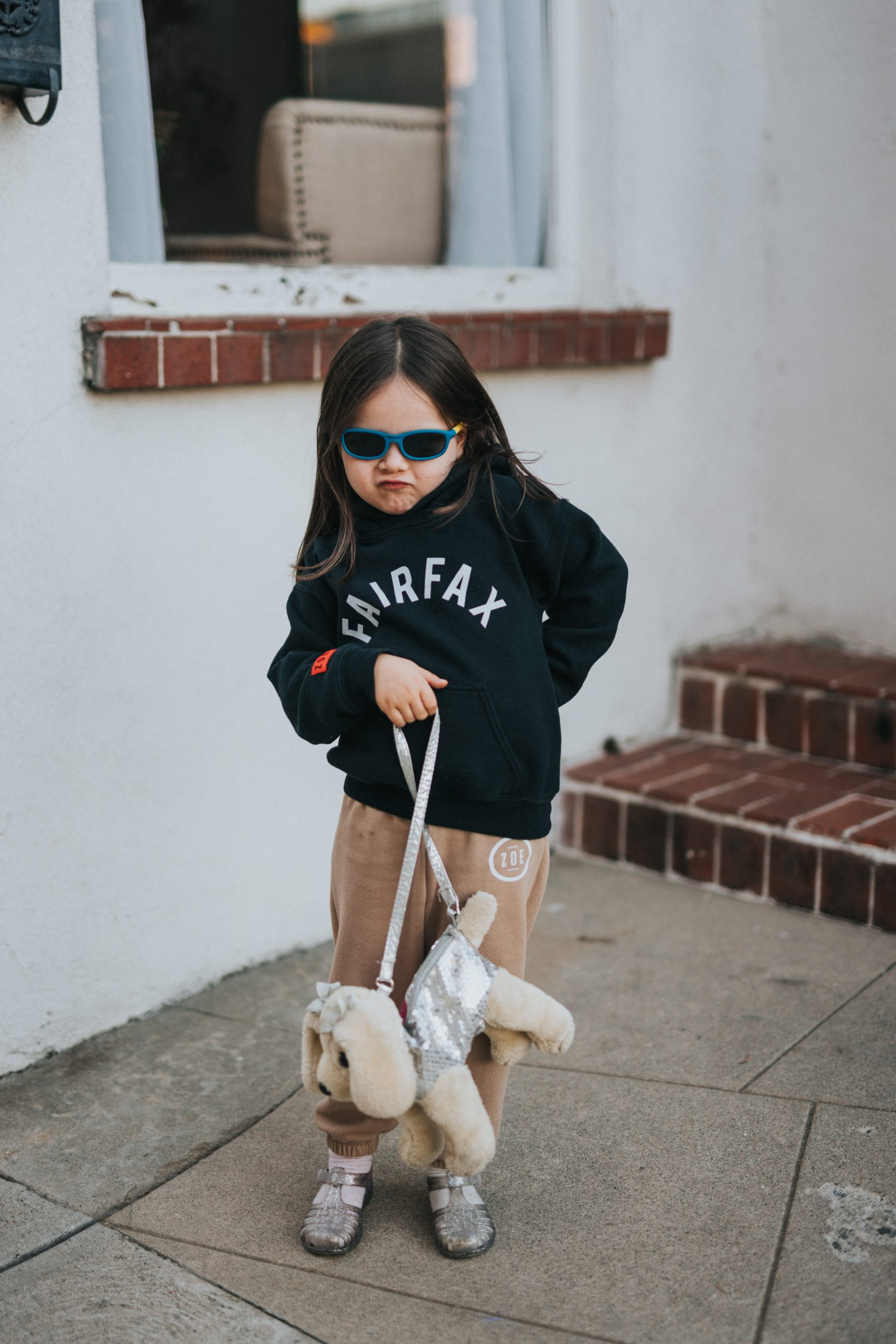 young girl wearing sunglasses and holding a dog purse